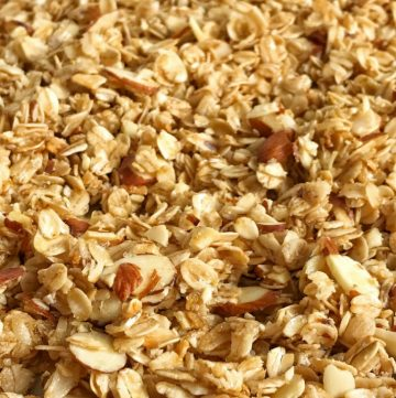 This coconut oil honey almond granola is loaded with whole grain oats + almonds and cooked in a sweet glaze of honey and coconut oil. It comes together in minutes and the taste is out of this world delicious! Plus, it's homemade with simple ingredients. Can't beat that.