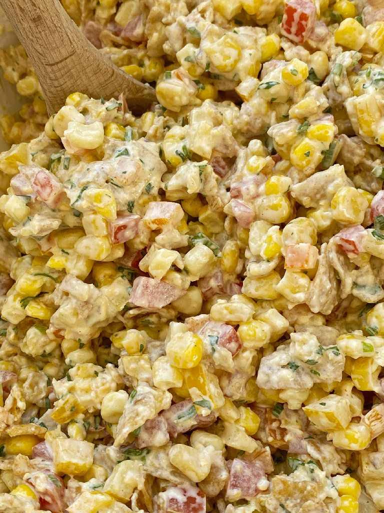 Fritos corn salad with corn, tomatoes, bell peppers, green onion, cilantro, and Fritos in a spiced creamy dressing. This is a salad no one will forget.