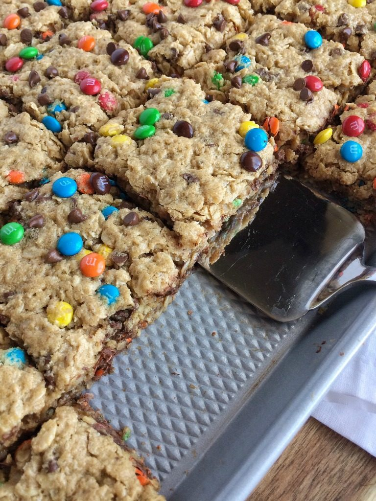 Monster cookie bars loaded with oats, peanut butter, chocolate chips, and m&m's. Plus, they have no flour in them! No flour monster cookie bars are delicious and perfect for a crowd.