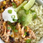Slow cooker chicken taco burrito bowls are a fuss-free, minimal prep & ingredients, and a family favorite dinner recipe. Cheesy chicken taco meat is made in the slow cooker! Create your very own burrito bowl, at a fraction of the cost of take-out, right at home. Cheesy chicken taco meat served over some cilantro lime rice and topped with avocado, sour cream, green onions, and whatever else you want | www.togetherasfamily.com #chickenrecipes #tacorecipes #tacos #slowcookerrecipes #crockpotrecipes #burritobowls