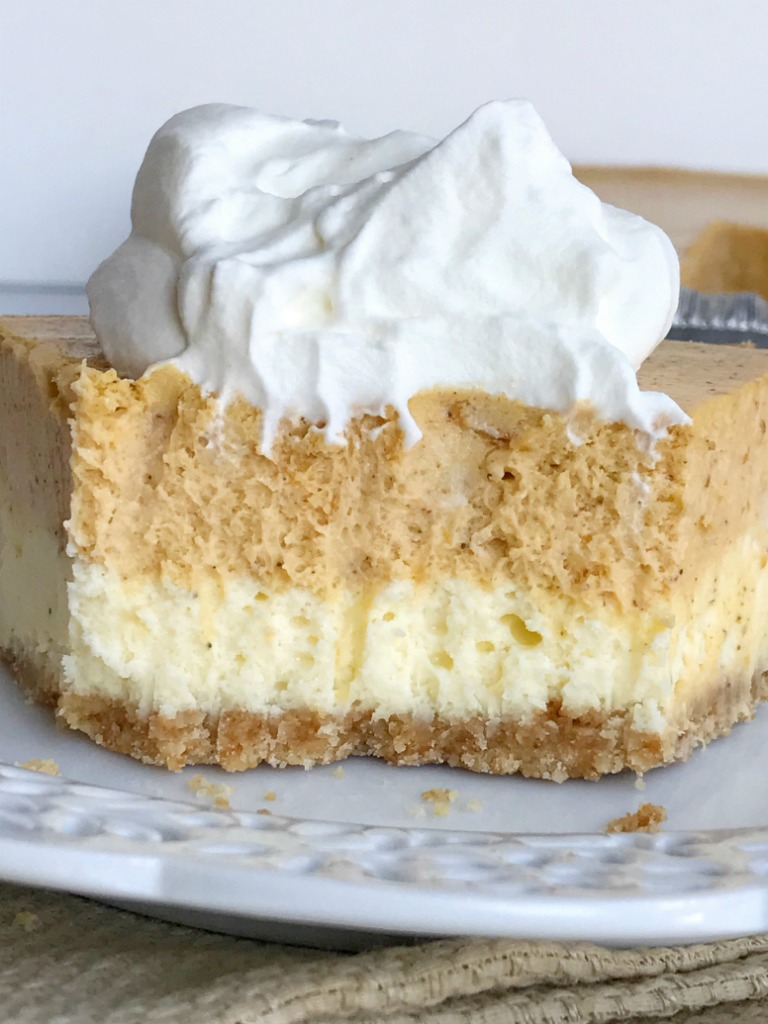 Double layer pumpkin cheesecake pie has two layers of pumpkin cheesecake inside a prepared graham cracker crust. This is an easy cheesecake recipe that even beginners can make. Top with some fresh whipped cream for the ultimate Fall dessert or add it to your Thanksgiving dessert table   www.togetherasfamily.com #pumpkin #pumpkinrecipes #cheesecakerecipes