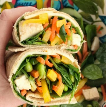 Sesame chicken vegetable wraps are a smart and healthy choice for lunch or dinner! Whole wheat tortilla filled with spinach, bell pepper, edamame, snap peas, cucumber, carrots, and chunked chicken and drizzled with a sesame citrus dressing | Together as Family #healthyfood #healthyrecipes #wraps #wraprecipes