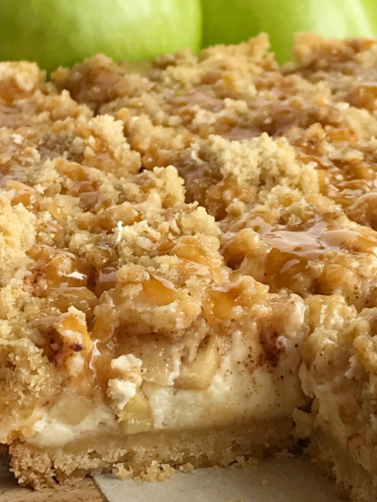 Caramel Apple Cheesecake Bars have a short bread crust, creamy cheesecake, cinnamon sugar apples, and a brown sugar oat crumble. Drizzle with caramel sauce for a delicious apple dessert recipe.