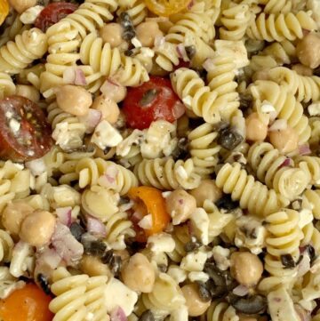 Greek Pasta Salad   Pasta Salad Recipes   Easy Greek Pasta Salad with tender spiral pasta, feta cheese, black olives, cherry tomatoes, red onion, and chickpeas with a easy dressing of Greek Vinaigrette salad dressing. So much flavor and texture, it's sure to be a hit. #salad #pastasalads #greek #sidedish #summerrecipes #pastasaladrecipes #recipeoftheday