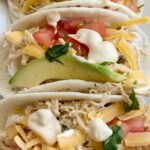 Slow Cooker Chicken Queso Tacos | Tacos | Chicken Tacos | Chicken Tacos made in the slow cooker with only 4 ingredients! Shredded chicken with queso, inside a flour tortillas with all the toppings you love. These queso chicken tacos are so easy and full of creamy queso flavor. #tacorecipes #tacos #dinner #dinnerrecipes #chicken #chickenrecipes #recipeoftheday