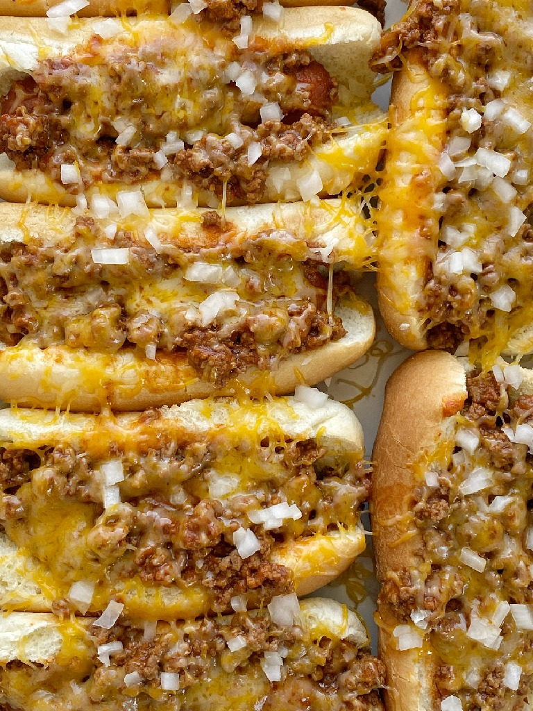 Slow Cooker Chili Coney Dogs are so simple to make in the slow cooker! Hot dogs and the savory ground beef meat sauce cook together in the crock pot. Serve in hot dog buns and top with shredded cheese and finely diced white onion.